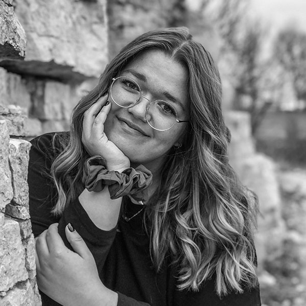 A black and white photograph of Megan Wiebe, smiling and leaning against a rock wall in a quarry