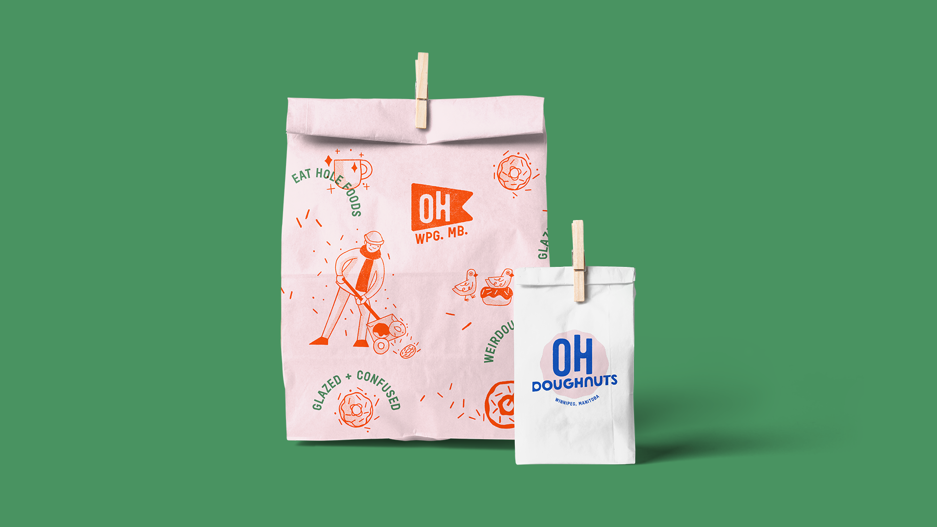 """Two doughnut bag designs. The larger one is pink with red and green type and illustrations. The type content is an assortment of doughnut puns like """"Glazed and Confused"""" and others. Illustrations include a man shovelling doughnuts, a pigeon in a doughnut nest, and a girl riding a doughnut bike. The small bag features the Oh Doughnuts logo in pink and blue on a white bag."""