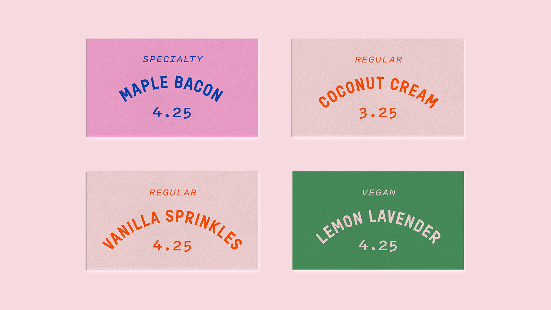 An image of four cards with doughnut names and prices. These cards would be displayed in a doughnut display. The types listed are vanilla sprinkles, lemon lavender, coconut cream and maple bacon. The type is on a circular path with the price below and the cards are colour coordinated based on vegan, regular and specialty doughnuts