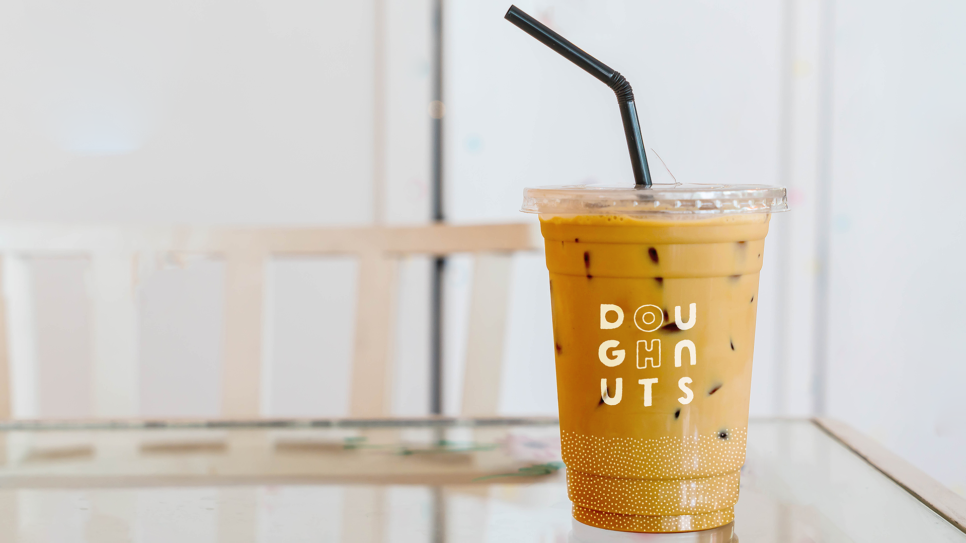 An iced coffee sitting on a table with the modular Oh Doughnuts logo on the front in white. A dot pattern goes around the bottom third of the cup.