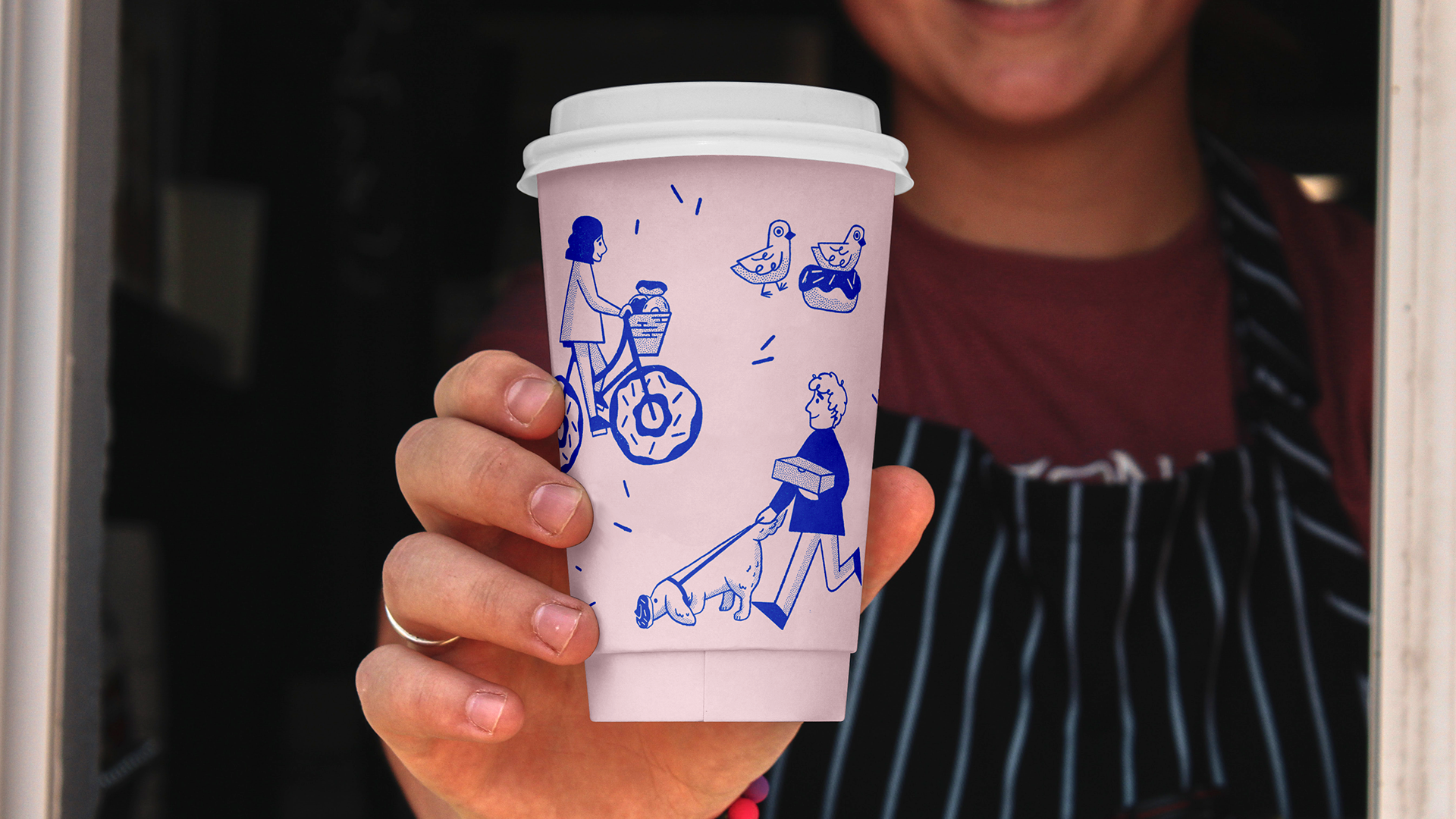 An image of a person holding out an Oh Doughnuts branded cup, featuring a pink background and blue illustrations of a man walking a dog with a doughnut on it's nose, a girl riding a doughnut bike and a pigeon sitting on a doughnut nest.